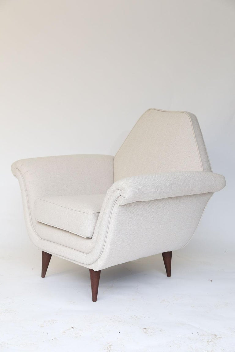 Petite in size and full of midcentury style, this pair of French Mid-Century Modern chairs is sure to delight. Newly restored and upholstered in a linen blend fabric and standing on wood angular legs, these chairs will withstand the test of time.