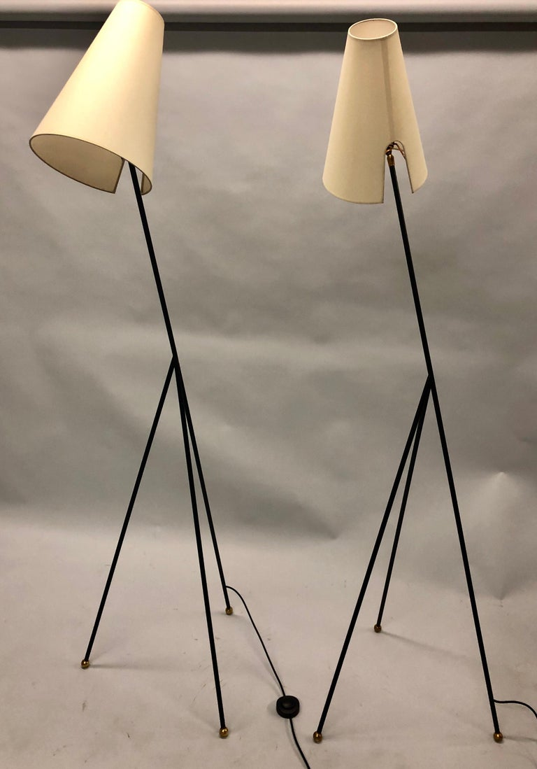 Elegant, sculptural pair of French Mid-Century Modern enameled wrought iron floor lamps attributed to Disderot   The standing lamps have a stunning triangulated form, elegant tapered legs terminating in brass ball finials and finished with conical