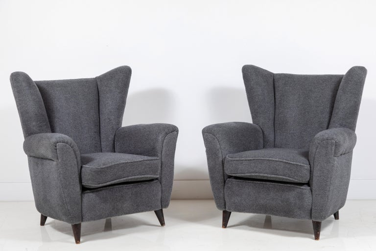 Pair of French midcentury wingback chairs upholstered in a grey mohair. Original fabric and original finish on the legs.