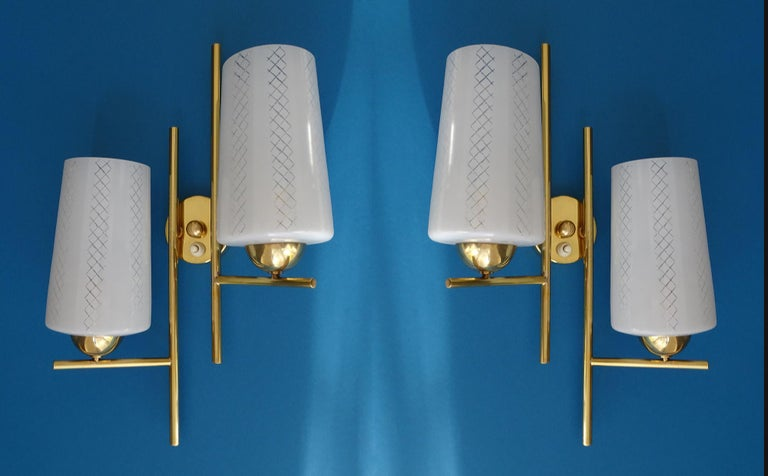 Pair of  French, architectonic modernist sconces by Lunel, circa 1965 . They  feature two opaline glass shades with a criss-cross pattern mounted on an asymmetrical brass structure, brass glass holders cups and central piece covering the wall mount.