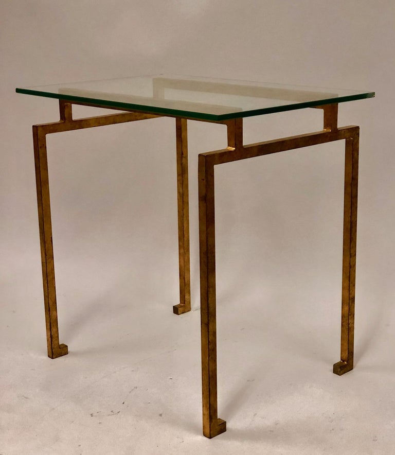 A pair of French midcentury style side or end tables in the modern neoclassical spirit. The tables are in gilt handwrought iron with delicate turned in sabots in the Egyptian taste.   Literature: Similar pair sold at Sotheby's New York, Important