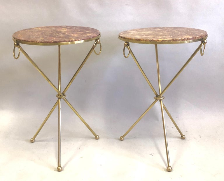 Elegant and timeless pair of French Mid-Century Modern neoclassical brass and marble side or end tables in the style of Jean-Michel Frank.   The gueridons or tables are constructed in solid brass resting on tripod legs ending in ball feet. They