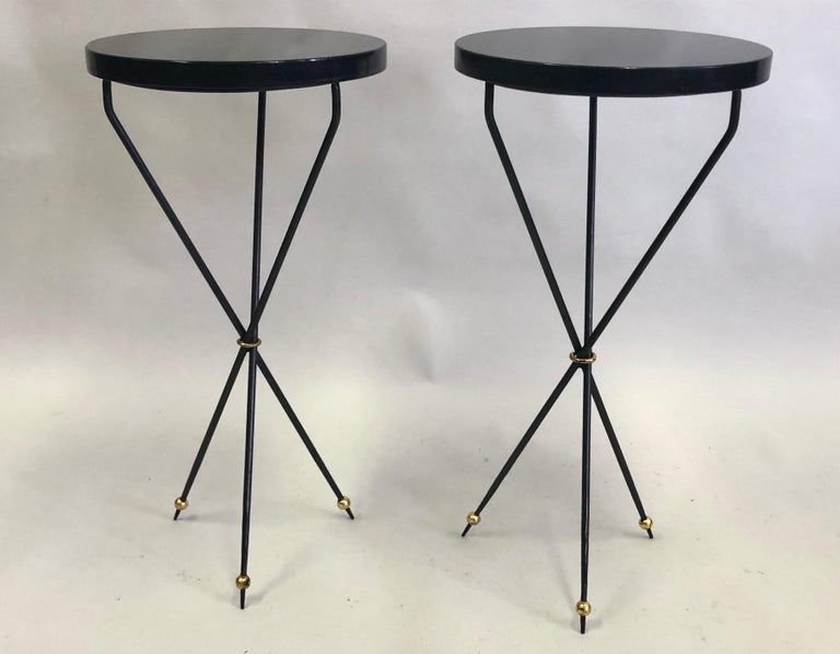 A delicate, refined pair of French Mid-Century Modern neoclassical side or end tables / gueridons in the spirit of Jean Michel Frank. The pieces are composed of a pure, sober, minimal, yet dramatic tripod form. The legs are long, thin and angled