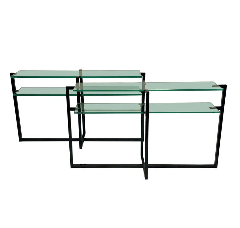 A matched pair of French Modernist console tables, in black hand lacquered steel, each with double shelves in thick plate glass.