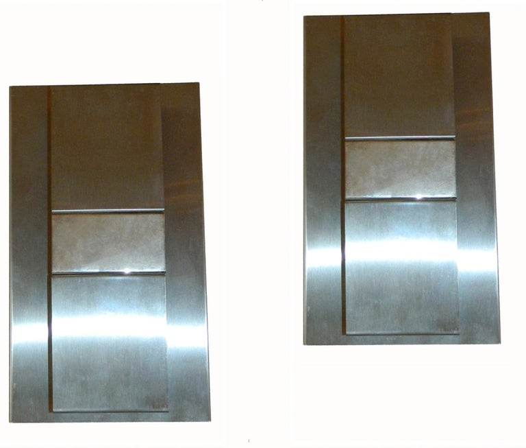 Pair of rectangular brush streel and polished metal wall sconces. 2 bulbs by sconce. Max wattage: 40w/bulb. 2 pairs available.
