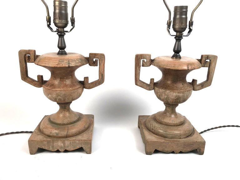A stylish pair of French carved wood urn-form lamps, with geometric strap handles on scalloped square bases. Newly electrified. Perfect for bedside tables, a console table or ambient lighting in a variety of rooms. Height of wood vases: 9.75