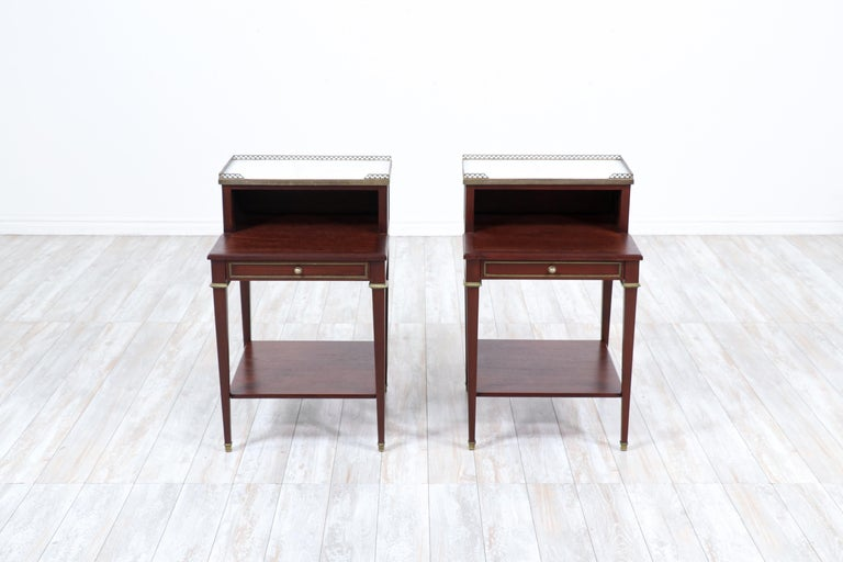 """An exceptional pair of French 1930s mahogany nightstands in the neoclassical style.  These wonderful 2 tier nightstands feature a rich mahogany grain, Carrara marble tops, brass galleries and ormolu details.   Newly refinished and in """"showroom"""""""