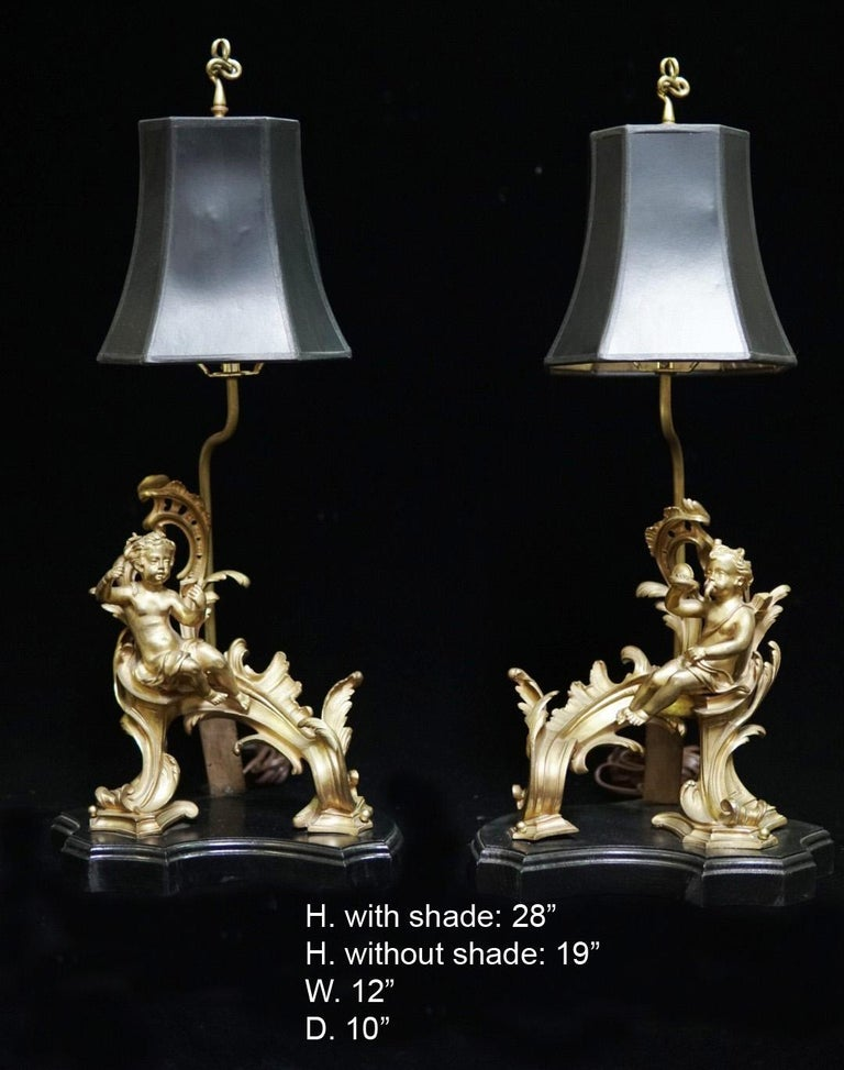 Pair of French ormolu chenet mounted lamps with black rectangular shades, Late 19th century. Each lamp is mounted with a ormolu acanthus motif chenet with a putti, raised on a conforming stepped black base.  Shades not