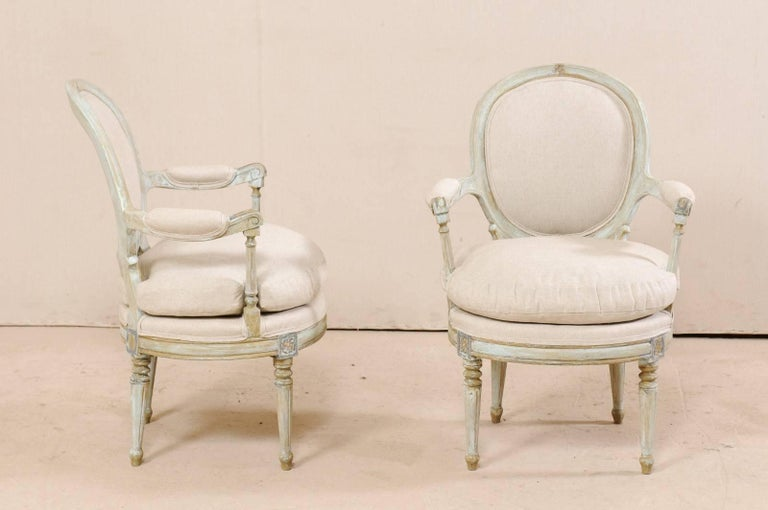 Pair of French Oval-Back Bergère Chairs with Delicately Carved Floral Motifs In Good Condition For Sale In Atlanta, GA