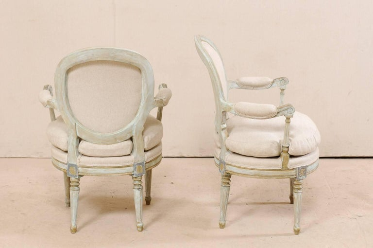 20th Century Pair of French Oval-Back Bergère Chairs with Delicately Carved Floral Motifs For Sale