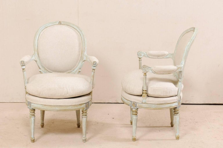 Wood Pair of French Oval-Back Bergère Chairs with Delicately Carved Floral Motifs For Sale