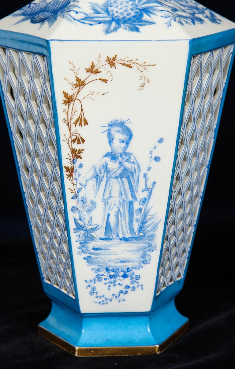 A beautiful pair of French Paris porcelain blue and white chinoiserie style open-work vases. Each is beautifully hand painted with tiffany blue chinoiserie figures of a boy and girl in a field. Each vase is decorated with a double-walled open
