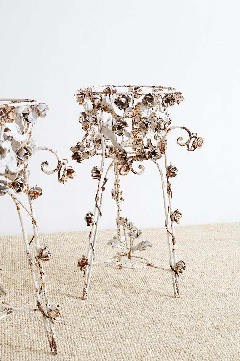 Gorgeous pair of French wrought iron jardinières or plant stands featuring a rich patinated metal finish. Covered with beautiful wrought iron roses and vines over a scrolled base with hairpin legs. Each scrolled leg has a hanging ring decorated with