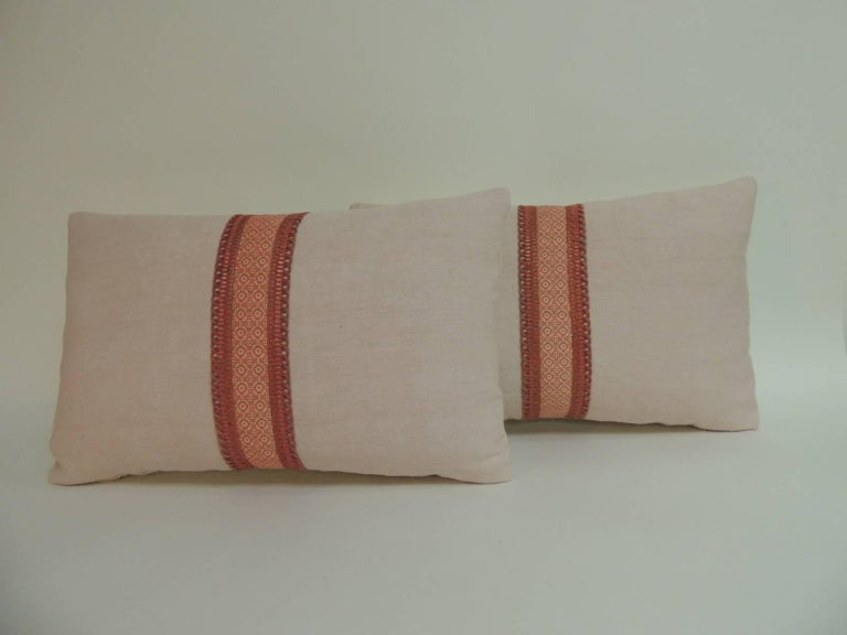 Pair of pink homespun linen decorative lumbar pillows embellished in the centre with a red and natural floral woven ribbon in a floral pattern. Accentuated with antique silk braided trim in red. Decorative pillows finished in natural linen. In
