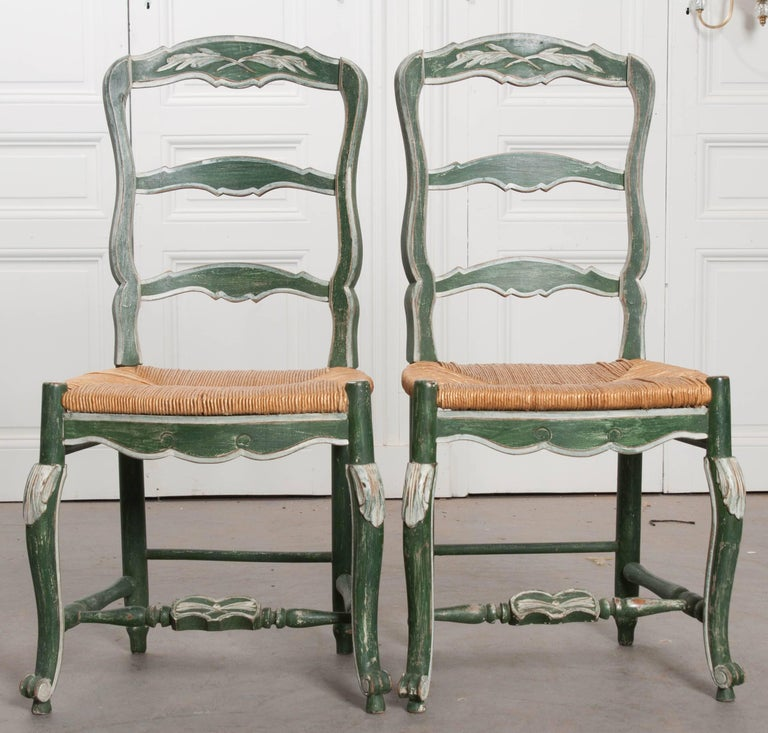 A pair of early 20th century Provincial rush seat ladder back dining chairs.  The chairs - Pair Of French Provincial Painted Rush Seat Chairs At 1stdibs