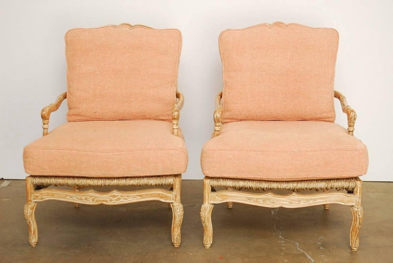 Bespoke pair of ladder back rush seat fauteuil armchairs or lounge chairs made in the French provincial style by William Switzer. Generous proportion frames hand made in Spain featuring a carved fruitwood finished in a white glaze. Fitted with deep
