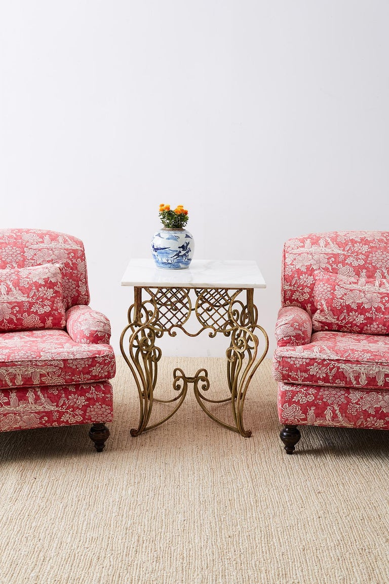 Fabulous pair of French Provincial toile oversized lounge chairs upholstered in a chinoiserie red toile de jouy printed fabric. Constructed with large heavy mahogany frames featuring an English rolled arm and a deep seat cushion. Very comfortable