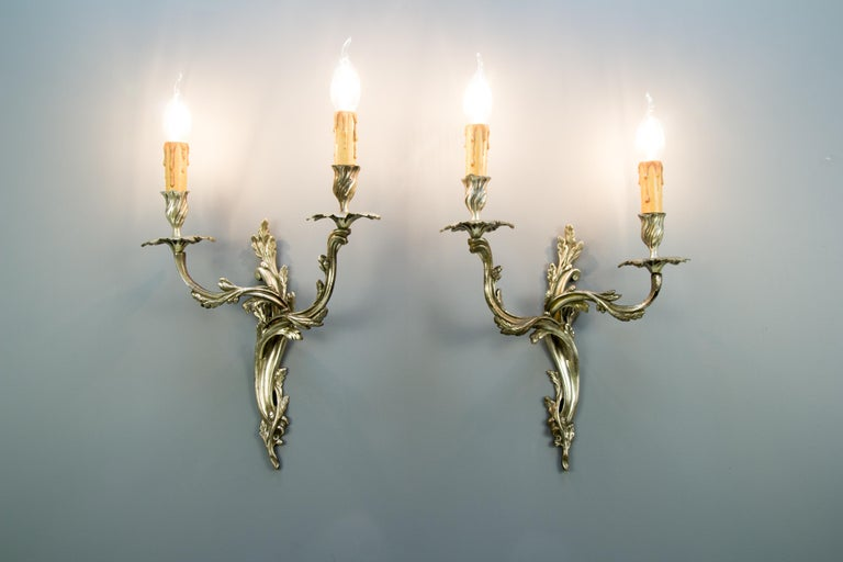 French Rococo or Louis XV style bronze sconces in silver color with ornate scrolled acanthus design. Each sconce has two branches with sockets for E 14 light bulbs.