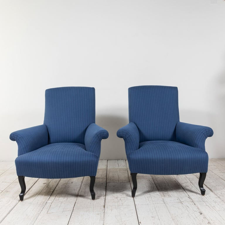 Classic pair of French rolled arm club chairs upholstered in tonal blue striped fabric from Howe of London. Original base finish boasts vintage flair.