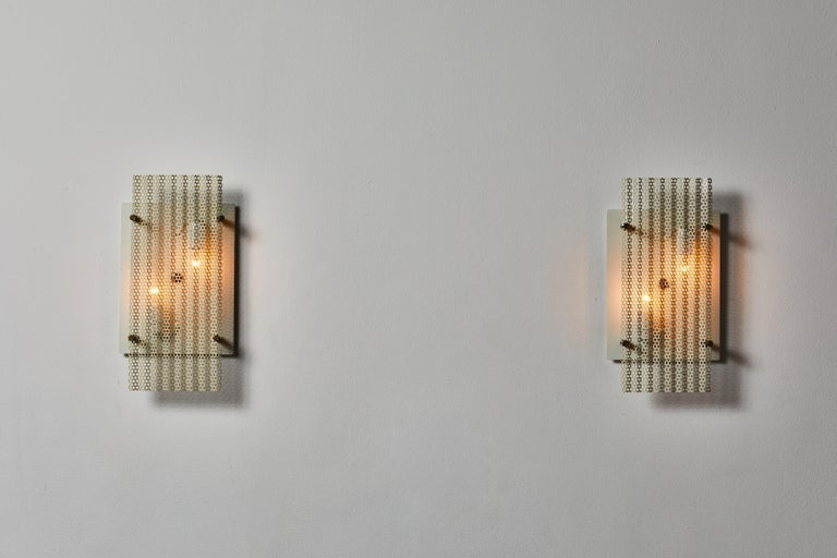 Pair of sconces manufactured in France, circa 1950s. Original painted perforated aluminum, brass. Wired for U.S. standards. We recommend two E14 40w maximum candelabra per fixture. Bulbs provided as a one time courtesy.