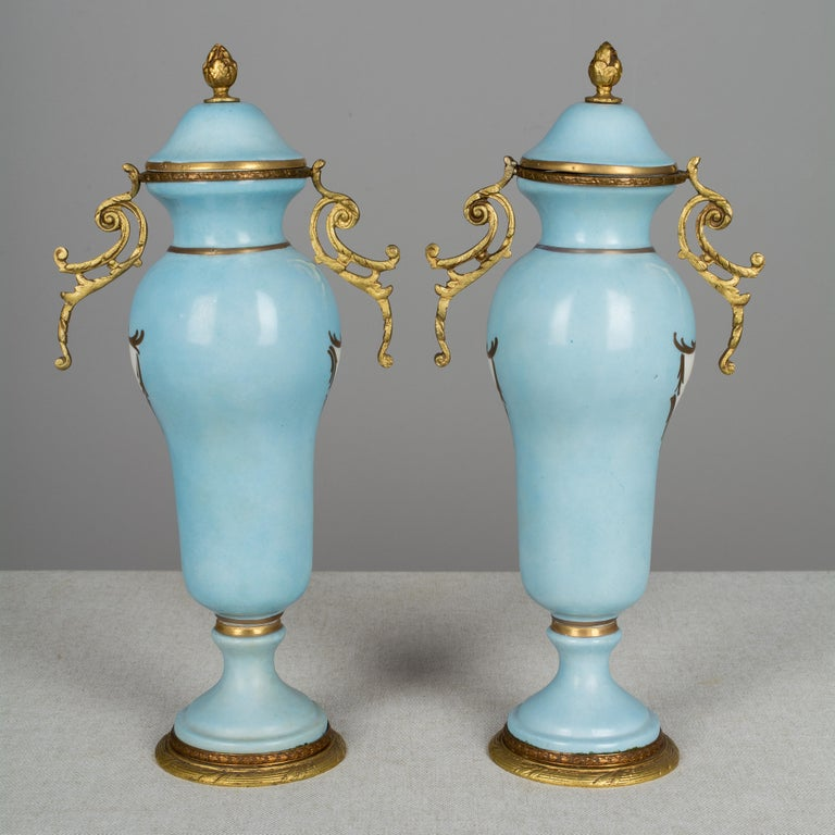 A pair of 19th century French Sèvres Porcelain bronze mounted urns, each with pastoral scenes on blue ground with hand painted gold accents. Marked on bottom.