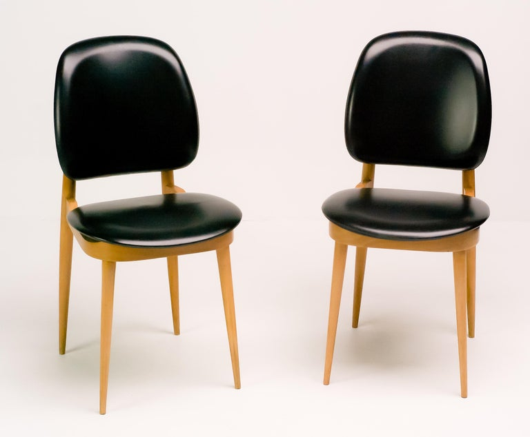 Pair of elegant chairs in maple and black vinyl.