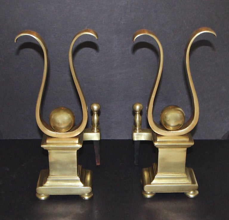 Pair of heavy solid brass lyre shape motif andirons. A stylized version of a Classic silhouette that can blend with both traditional and eclectic interiors.