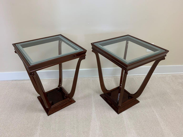 Pair of Art Deco streamline tulip shaped glass top side tables. This simple and elegant design from the period has frosted edge glass tops that are supported by gentle curving legs on tapered bases. These tables were professionally restored in a
