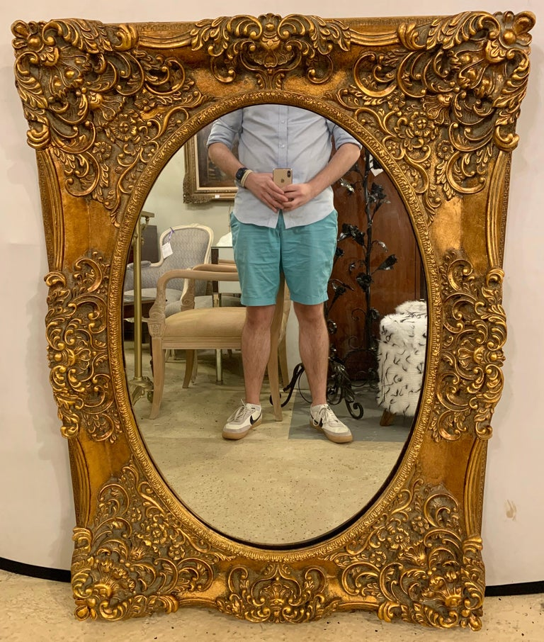 Pair of French Style Wall, Console or Pier Mirrors. Gilt Gesso and Wooden. These finely crafted oval mirrors set in a heavily carved wood and composition frame. 