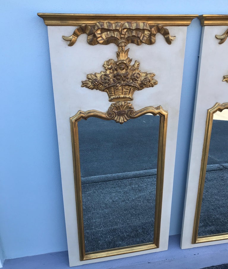 Pair of French Trumeau style mirrors in the 18th century design featuring a flower basket motif. Antique white finish with gold leaf.