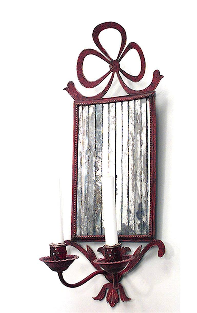 Pair of French Victorian style red tole bow knot wall sconces with mirrored back and two arms (20th century).