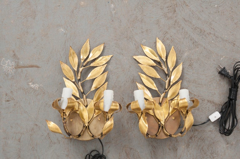 "A fabulous pair of French vintage gilt-brass ""laurel leaf"" two-light sconces, circa 1970s, each light fashioned to appear as if sitting upon a melted candlestick."