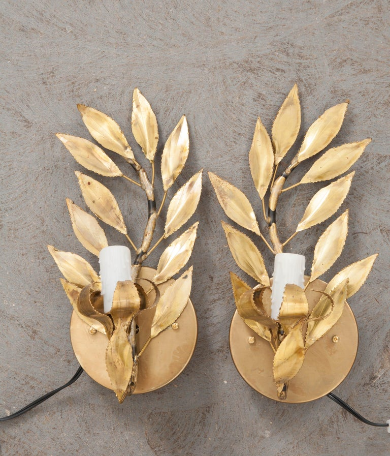 """A fabulous pair of French vintage gilt-brass """"laurel leaf"""" single-arm sconces, circa 1970s, each light fashioned to appear as if sitting upon a melted candlestick."""