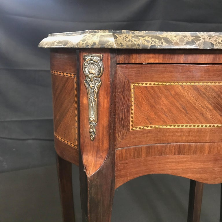 Great looking leggy nightstands, bedside tables or side tables, each with a dovetailed drawer with bronze wreath pull. French cabriole legs sit below the case with brass jabots and feet. Geometric inlay on drawer fronts, sides and backs of each