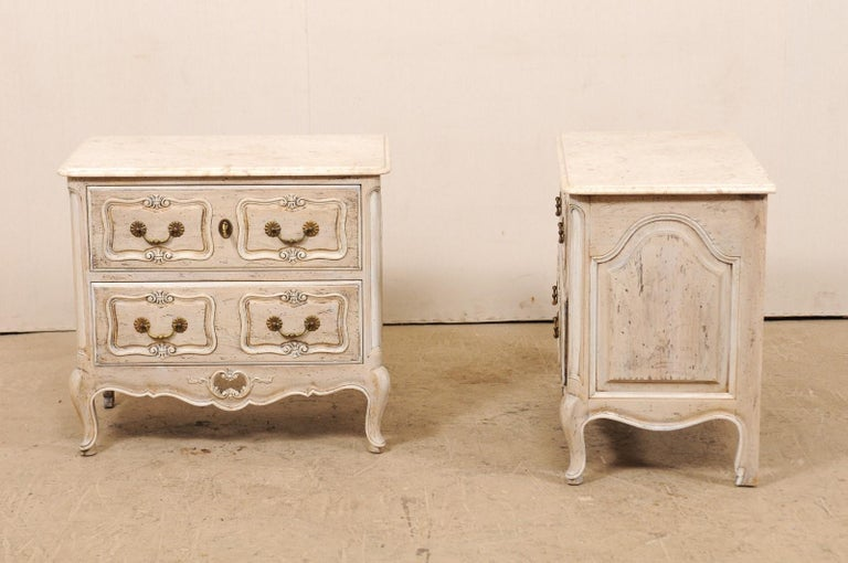 A pair of French two-drawer side chests with marble tops from the mid-20th century. This pair of vintage commodes from France each feature a stone top with an ogee bull edge and rounded corners, resting atop a wood case of cartouche carved panel