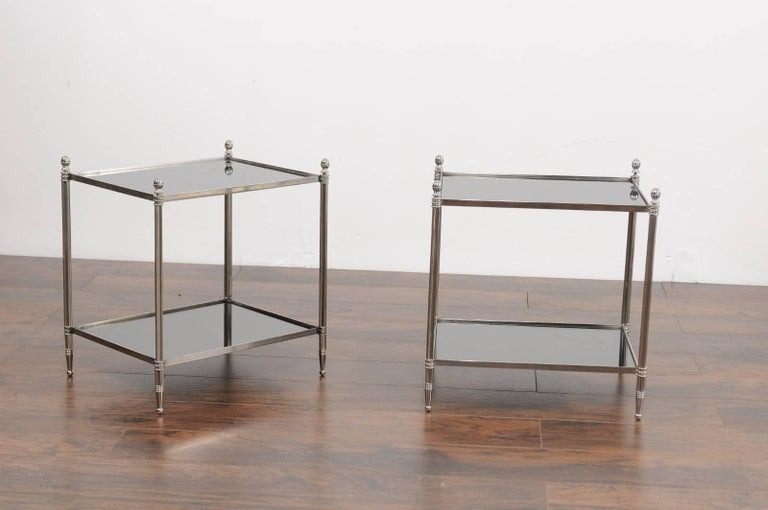 A pair of vintage French midcentury steel and mirrored glass tiered side tables. Each of this pair of French side tables features a sleek steel structure, supporting two rectangular mirrored shelves. The linear silhouette is made of four fluted