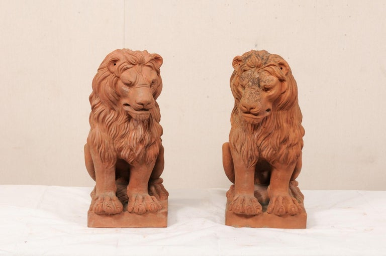 A pair of French vintage terracotta lions. This pair of lions from France, standing approximately 2 feet in height, each feature abundantly flowing manes, an attentively snarling face, nicely carved feet, and good definition of the rib cages on