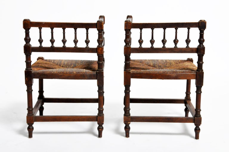 This pair of wooden corner chairs is from France and was made circa 1900. Strong and sturdy, the chairs feature comfortable rush seats and are suitable for everyday use.