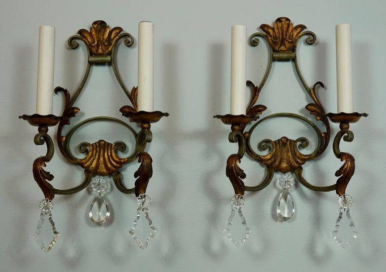 Pair of French provincial wrought iron sconces with cut crystals and gilt tole leaf details. Wrought iron is painted a light green color. To be rewired for use in the US.