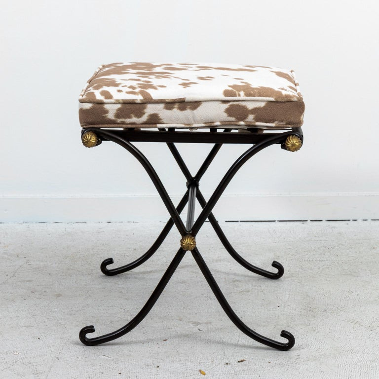 Wrought iron benches with brass ball medallion accents and faux hide print upholstery, circa mid-20th century. Made in France in the French Directoire style.