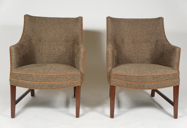 A pair of Danish modern armchairs by noted designer, Frits Henningsen, from the 1940s, newly upholstered in a light beige tweed with beige leather piping and with mahogany frames, the curved arms and relaxed back made for comfortable sitting.