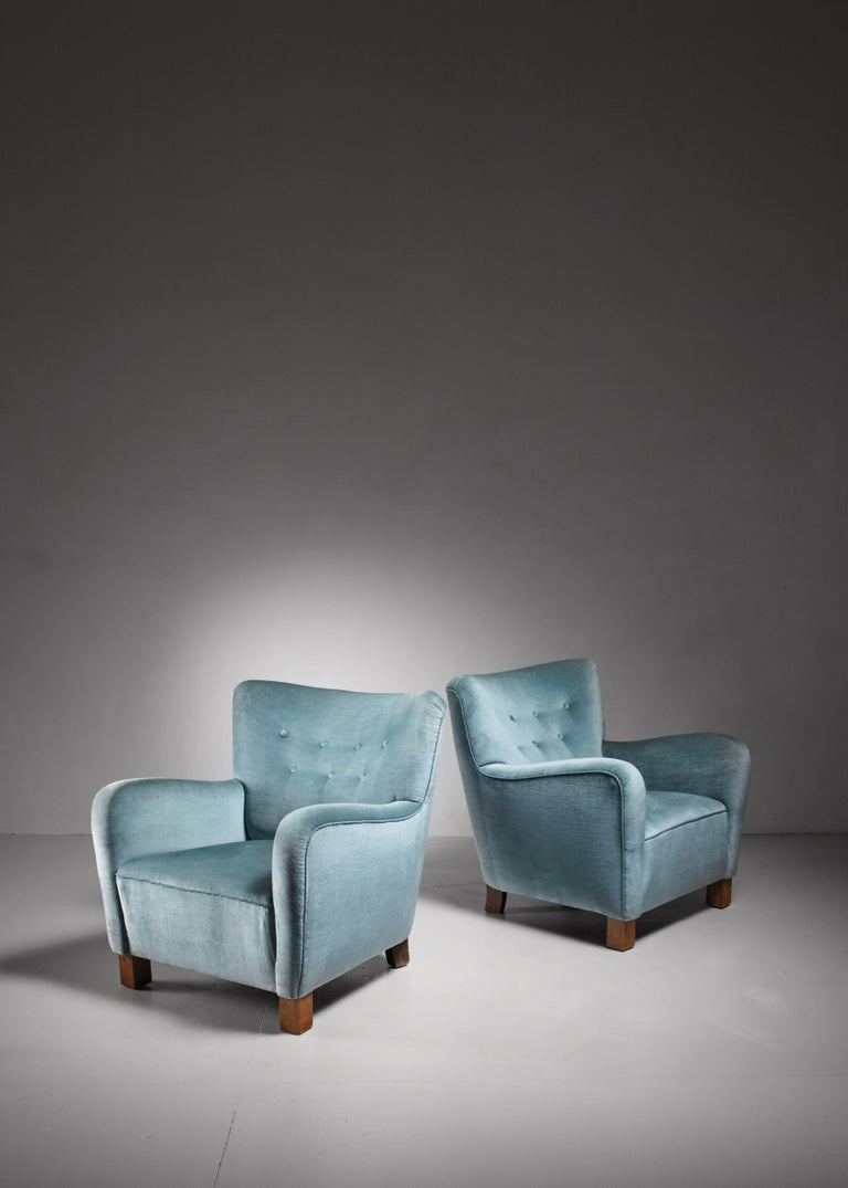 A pair of Danish lounge chairs with a blue, buttoned velvet upholstery. The chairs are a variation on model 1669 by Fritz Hansen. A wonderful and comfortable pair.