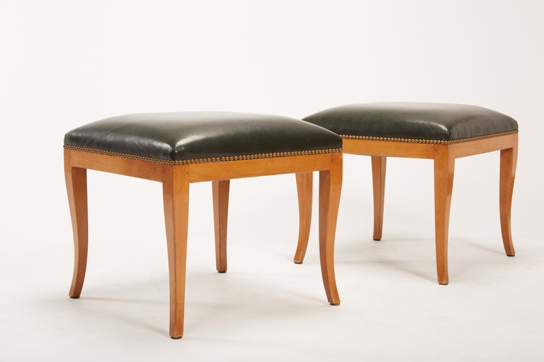 Pair of fruitwood Biedermeier style ottomans or stools with blackish green leather and bronze tone brass tacks. Construction of legs includes square pegs for mortise and tenon joints. Restored in 2004, with new leather, brass tack and refinishing.