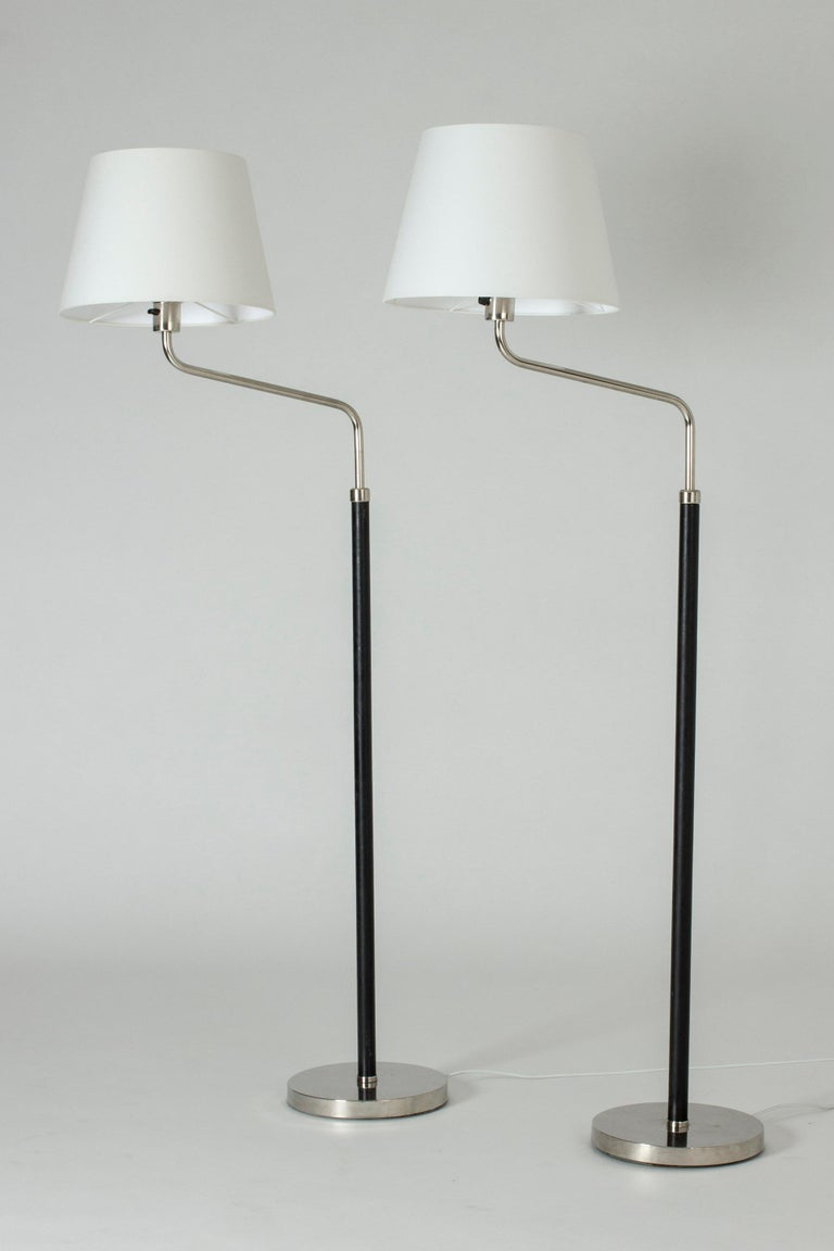 Pair of cool functionalist floor lamps by Bertil Brisborg. Made from steel with leather dressed poles.