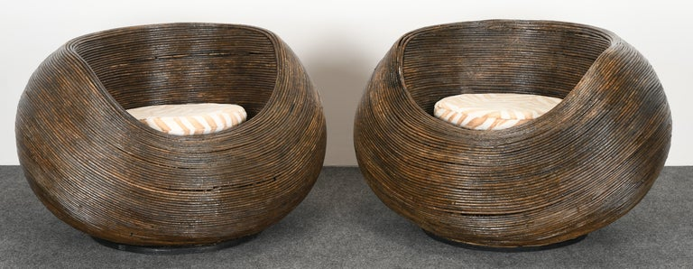 A pair of rattan pod lounge chairs. These chairs have great style and we believe they are vintage but are unsure of age. Some damage to rattan, as shown in images, which may need restoration.  Dimensions: 25