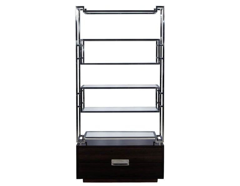 These American designed bookcases features geometric stainless steel frames that supports six floating glass shelves. The gorgeous Macassar Ebony base includes two drawers accented with stainless steel pulls. A modern yet timeless addition to any