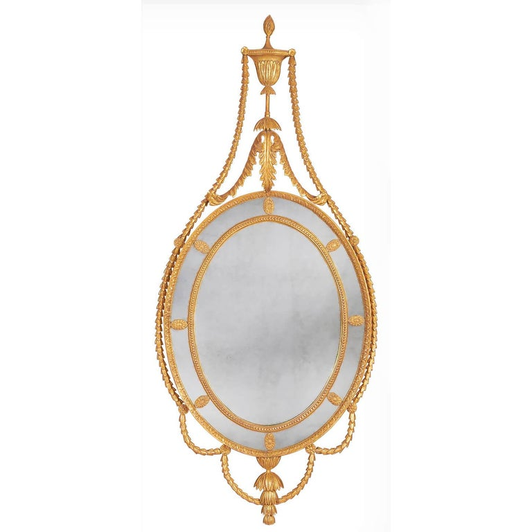 A pair of carved giltwood George III mirrors of Adam design with leaf carved outer frame and bead carved inner frame, the surrounding border glasses are punctuated by oval flower-head paterae. The cresting formed of a classical urn. The flame finial