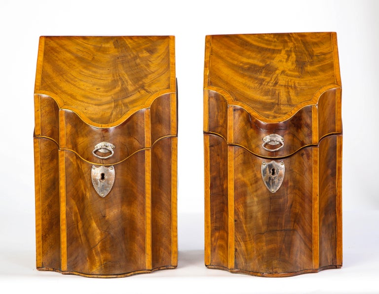 Two George III inlaid mahogany cutlery boxes from the late 18th century. Each box has a hinged top, with a sloping serpentine front and shield-form escutcheon plates. Both enclose a retrofitted wooden interior for stationery or organization of a
