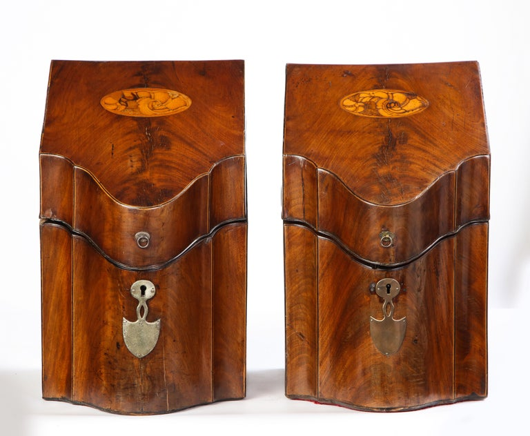 Pair of George III inlaid satinwood cutlery boxes, late 18th century. Each with a sloping serpentine-front hinged top inlaid with a decorative shell design, metal escutcheon plates, and enclosing a fitted interior.  Some of the most celebrated