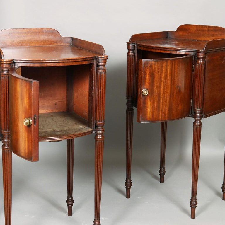 A very useful pair of late 18th century bedside cabinets Crafted from the finest South American mahogany With curved opposing doors and raised on tapering fluted legs in the manner of Gillows The grain of the mahogany veneer is laid vertically